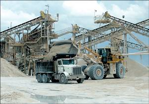 a front loader putting gravel into a dump truck with conveyors and piles of gravel in the background