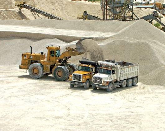 a front loader filling a dump truck with gravel near a large pile of gravel with processing equipment visible in background