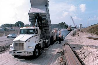 a dump truck emptying its load of asphalt for a paving crew