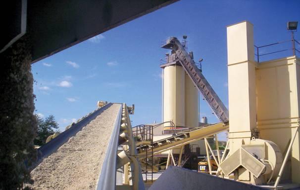 an inclined conveyor belt moving gravel at an asphalt plant
