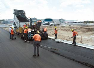 a paving crew spreads and sweeps asphalt from a dump truck and paver