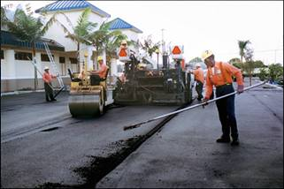 a worker raking asphalt laid by a paver while a road roller compacts it