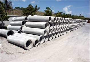 two long rows of concrete pipes stacked four high