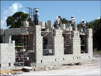 four workers making a building out of concrete blocks