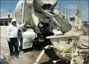 a cement truck driver emptying his truck into a hopper