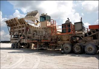 High-capacity loaders bringing recovered limestone to a portable road rock crusher
