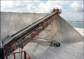 an output conveyor belt from a portable rock crusher creating mounds of crushed gravel