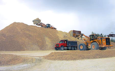 Using high-capacity Cat 988H front-end loaders, Horatio Cortez adds material to a stockpile while Carlos Vargos quickly and efficiently loads a customer's truck. (Photos by Carl Thiemann)