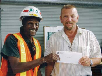 """Gary Moorer receives a check from Tim Blaisdell for his slogan, """"Safety is Free; Don't Pay with Your LIfe!"""""""