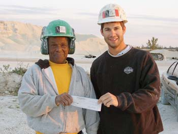 Constantine Campbell receives a check from Nick Rudanovich for creating the slogan shown on a quarry billboard, shown above.
