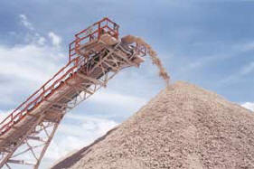 a conveyor belt making a mound of gravel